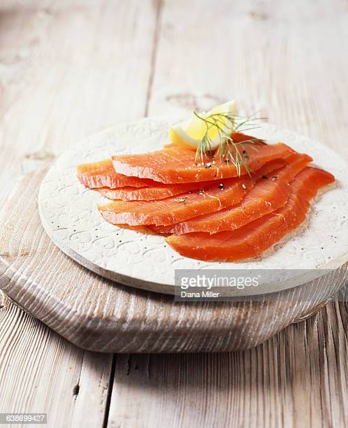 Smoked salmon slices with black pepper, dill and lemon