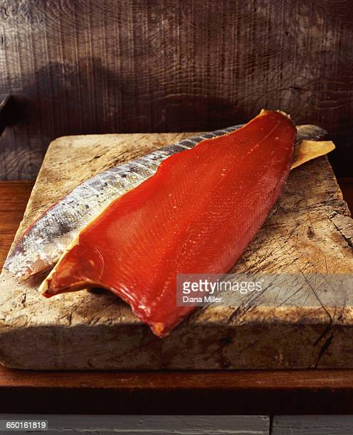 smoked side of salmon on wooden chopping board - smoked food fotografías e imágenes de stock
