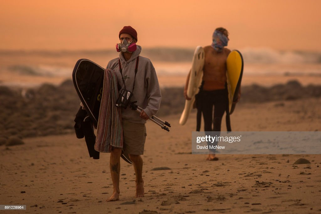 A smoke-filled sky filter orange light around surfers as the Thomas Fire continues to grow and threaten communities from Carpinteria to Santa Barbara on December 12, 2017 in Carpinteria, California. The Thomas Fire has spread across 365 miles so far and destroyed about 800 structures since it began on December 5 in Ojai, California.