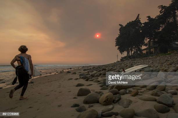 A smokefilled sky filters sunlight to orange around a surfer as the Thomas Fire continues to grow and threaten communities from Carpinteria to Santa...