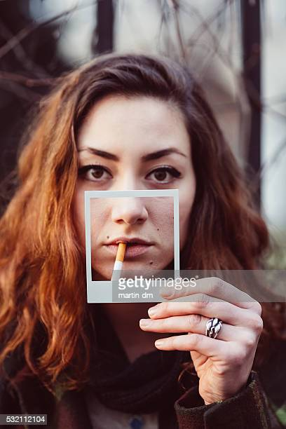 Smoker holding instant photo showing smoking damage to skin