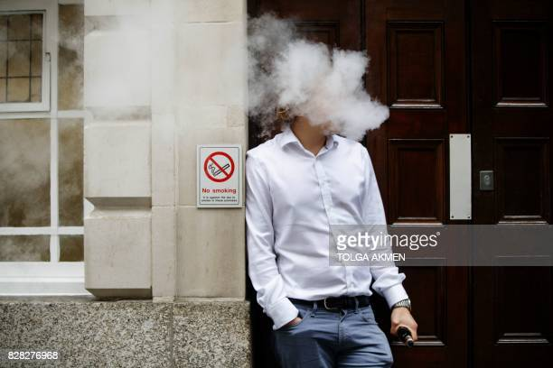 TOPSHOT A smoker is engulfed by vapours as he smokes an electronic vaping machine during lunch time in central London on August 9 2017 World stock...
