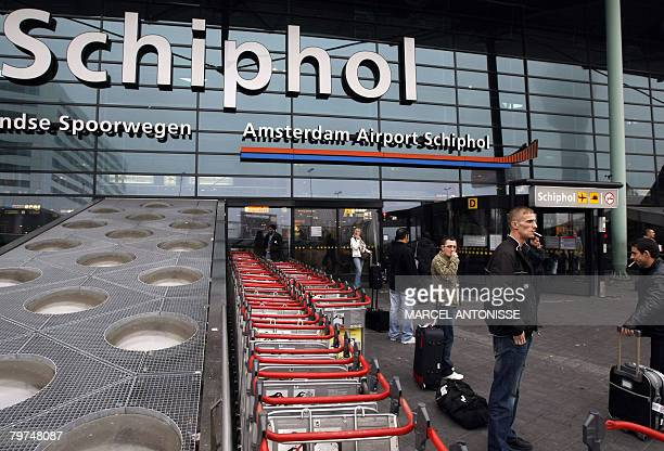 Smokers stand in front of the main entrance of Schiphol Airport in Amsterdam on February 14 2008 Smoking is prohibited in the airport Schiphol...