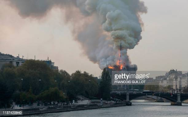 TOPSHOT Smokes ascends as flames rise during a fire at the landmark NotreDame Cathedral in central Paris on April 15 2019 afternoon potentially...