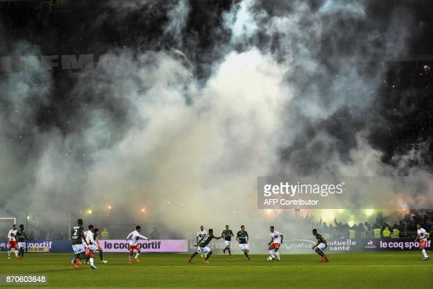Smokes fills the air after smoke bombs were lobbed during the L1 football match AS SaintEtienne vs Olympique Lyonnais on November 5 at the Geoffroy...