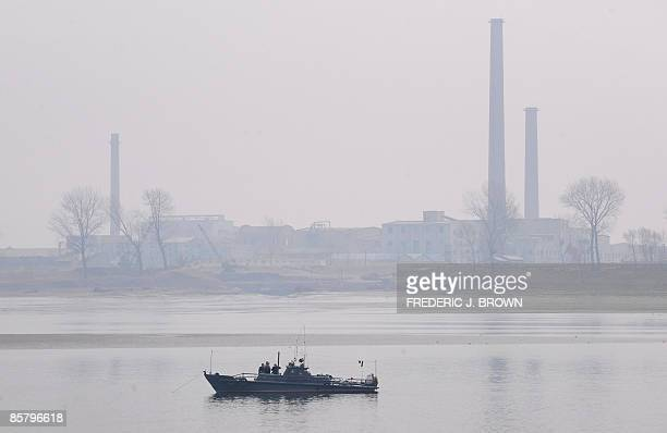 Smokestack chimneys line a hazy riverfront as a North Korean border patrol boat anchors in the middle of the Yalu River offshore from the North...