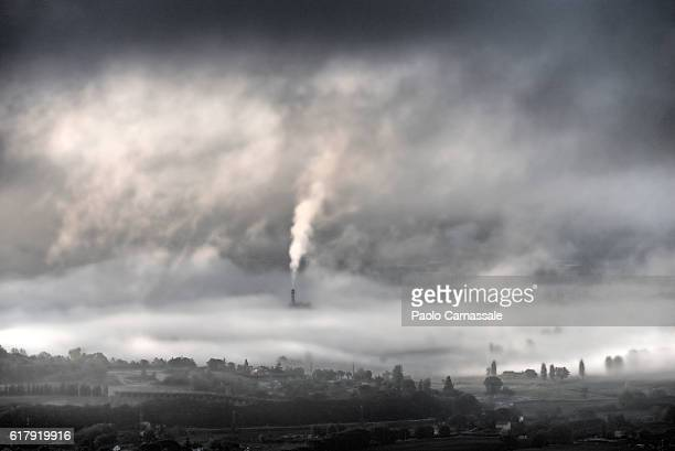 smokestack emerging from fog in terni, italy - smog stock pictures, royalty-free photos & images