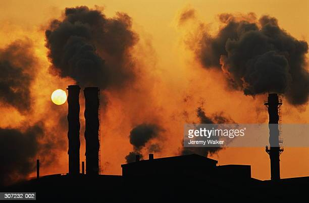 smokestacks at chemical plant silhouetted with setting sun behind - port talbot stock pictures, royalty-free photos & images