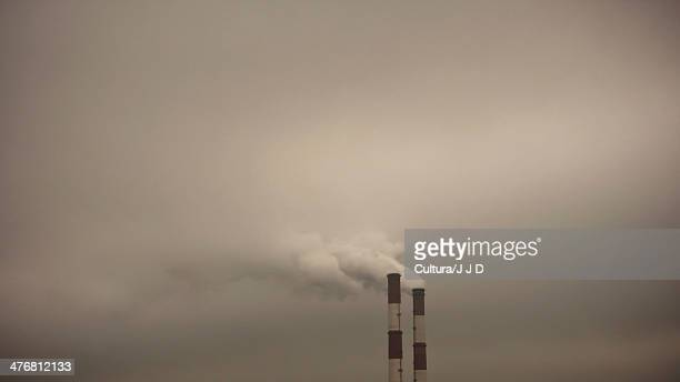 Smokestacks puffing in cloudy sky
