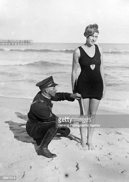 'Smokey' Buchanan from the West Palm Beach police force measuring the bathing suit of Betty Fringle on Palm Beach to ensure that it conforms with...