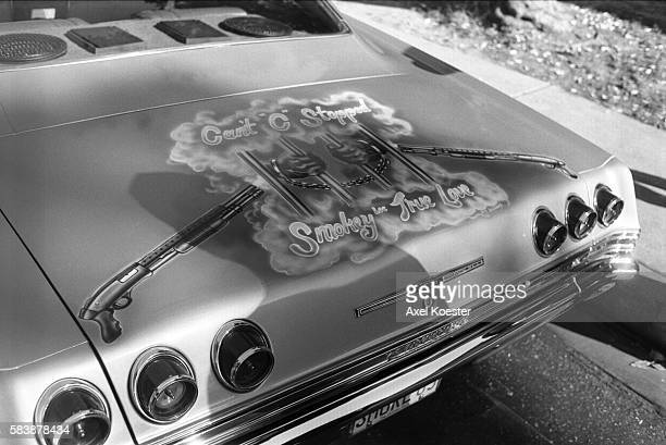 SmokeyLoc's 1965 Chevy Impala complete with hydrolics and classic lowrider styling features a painting showing two smoking shotguns on either side of...