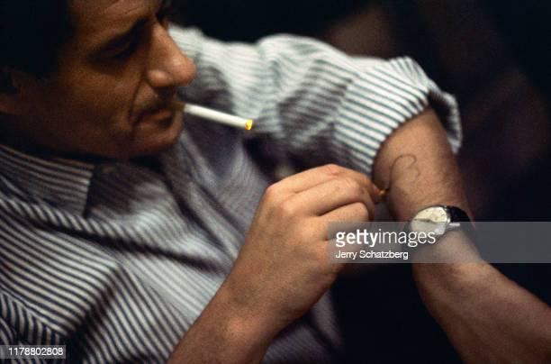 Smoking a cigarette, German-born Australian photographer Helmut Newton draws a heart on his arm, Paris, France, 1962.