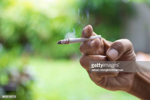 smoking a cigarette. smoking is harmful to health. - cigarette photos et images de collection