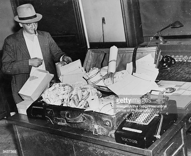 Smoking a large cigar PolishAmerican photographer Arthur 'Weegee' Fellig inspects an open suitcase full of stolen goods at a New York police station...