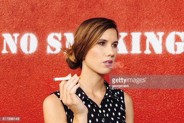 Smoking an e-cigarette in front of no smoking sign