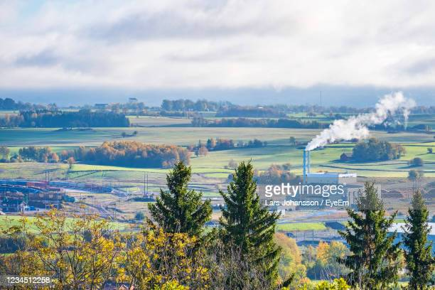smoking chimney on a heating plant in an industrial area - district heating plant stock pictures, royalty-free photos & images
