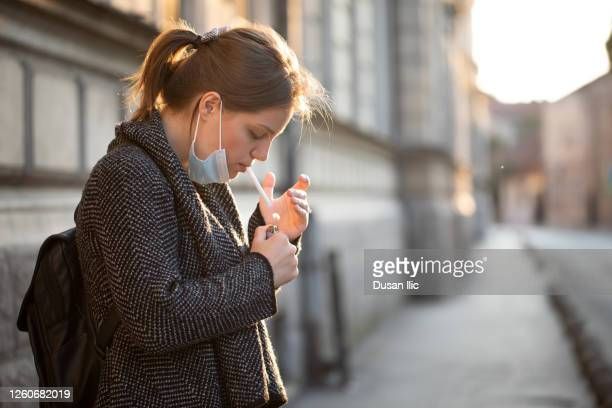 smoking cigarettes with mask - smoking issues stock pictures, royalty-free photos & images