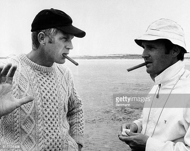 Smoking cigars actor Steve McQueen and director Norman Jewison discuss a scene from the movie The Thomas Crown Affair