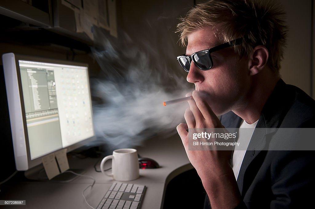 Smoking E-cigarette in secret in office : Stock Photo