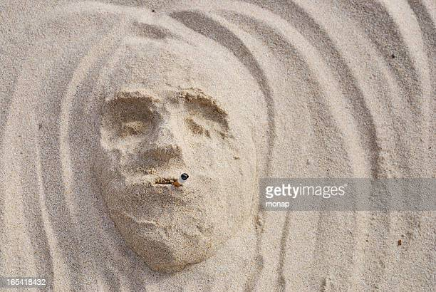 Smoking face in the sand