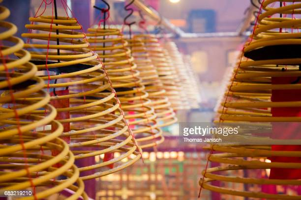 smoking incense coils in man mo temple - incense coils stock photos and pictures