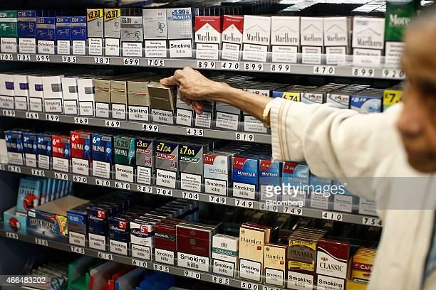 'Smoking Kills' and other warning labels sit on boxes of cigarettes as a shopkeeper reaches for a packet of Benson and Hedges cigarettes produced by...
