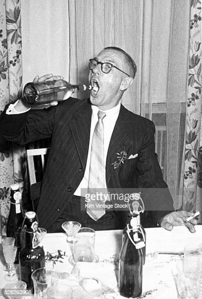 A smoking man playfully drinks from a liquor bottle while seated at a party