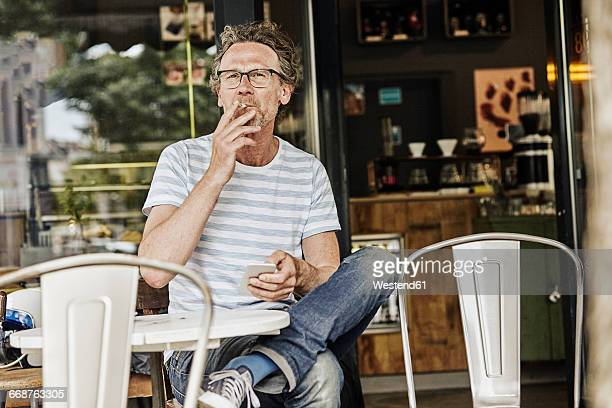 Smoking man sitting in front of a coffee shop