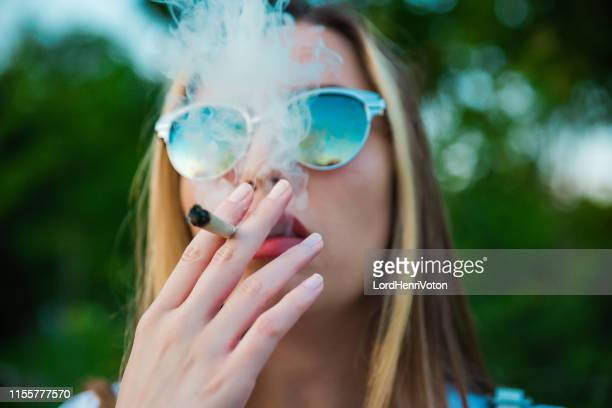 fumer de la marijuana - femme qui fume photos et images de collection