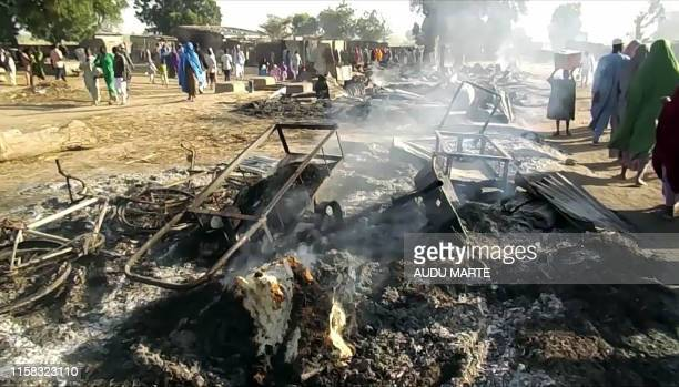 Smoldering ashes and charred items are seen on the ground in Badu near Maiduguri on July 28 after the latest attack by Boko Haram fighters on a...