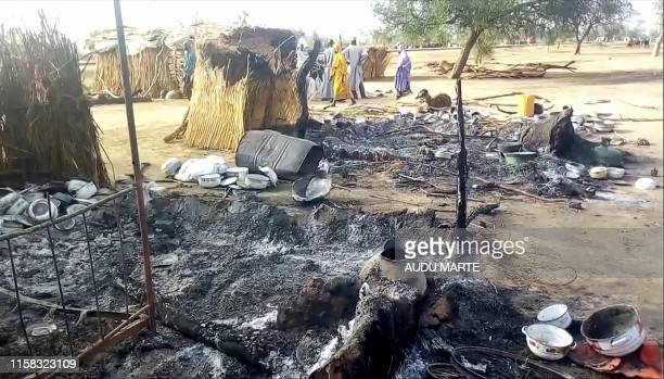 Smoldering ashes are seen on the ground in Badu near Maiduguri on July 28 after the latest attack this weekend by Boko Haram fighters on a funeral in...