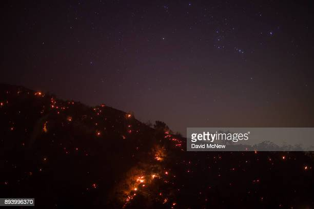 A smoldering mountainside is seen under the stars including the Orion constellation at the Thomas Fire on December 16 2017 in Montecito California...