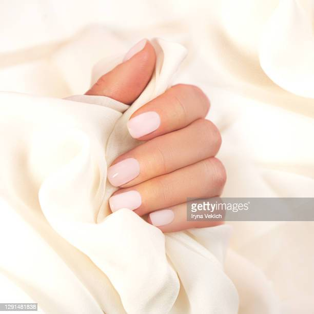 smooth elegant silk or satin and woman's hand with pastel color manicure. - beige stock pictures, royalty-free photos & images