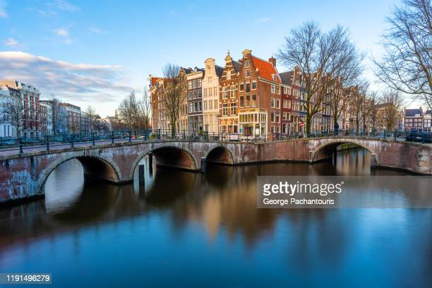 smooth reflections of houses in keizersgracht canal in amsterdam - olanda settentrionale foto e immagini stock