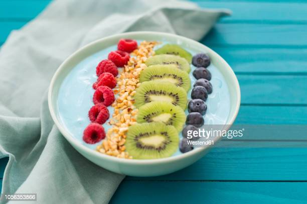 smoothie bowl with blueberries, raspberries, kiwi and chopped hazelnuts - tidy stock pictures, royalty-free photos & images