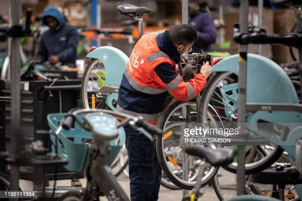 Smovengo employee repairs a Velib' bicycle for hire at the Villeneuve-la-Garenne Smovengo warehouse on January 17, 2020.