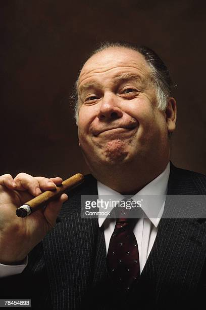 smug executive posing with cigar - fat cat stock photos and pictures