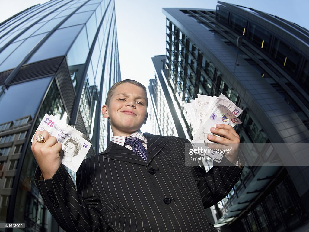 Smug Young Boy Wearing a Full Suit Stands in Front of Skyscrapers and Holding Wads of Banknotes : Stock Photo