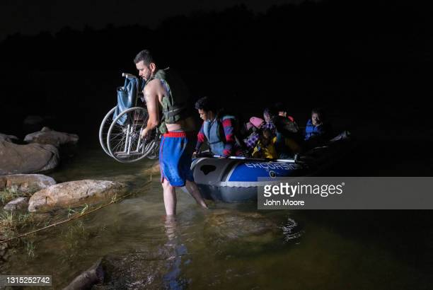Smuggler carries a wheelchair to the bank of the Rio Grande for 93-year-old Honduran immigrant Trinidad Tabora on April 29, 2021 in Roma, Texas. She...