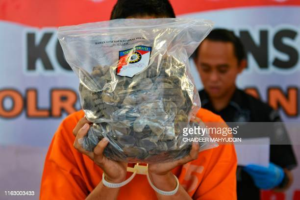 TOPSHOT A smuggler displays a bag of endangered pangolin scales during a press conference in Banda Aceh on August 21 2019