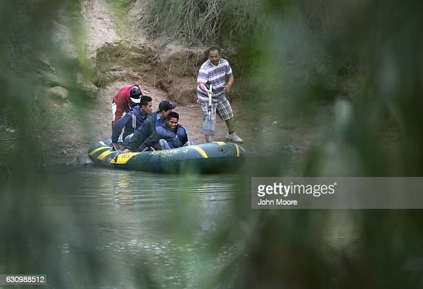 A smuggler pushes off a raft of undocumented immigrants to cross the Rio Grande from Mexico into the United States on January 4 2017 near McAllen...