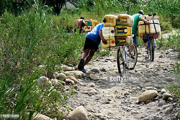 Smugglers push bicycles loaded with gasoline barrels on the shore of the river Tachira on the ColombiaVenezuela border on 2 May 2006 in La Parada...