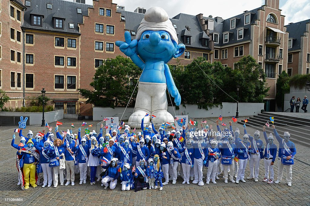 Smurf Ambassadors pose below a giant Smurf figurine for a group photo as part of Global Smurfs Day celebrations on June 22, 2013 in Brussels, Belgium.