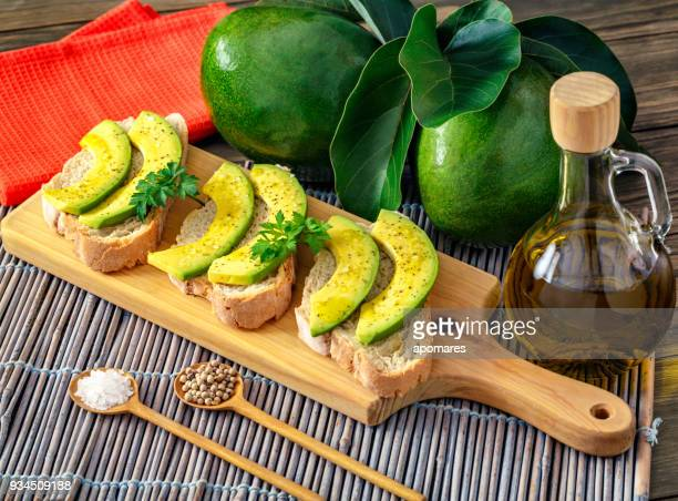 Snack or appetizer of avocado slices bruschetta with olive oil, peppermint and salt