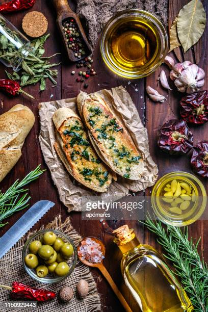 snack or appetizer of garlic basil and olive oil bruschetta on table in a rustic kitchen - italian food stock pictures, royalty-free photos & images