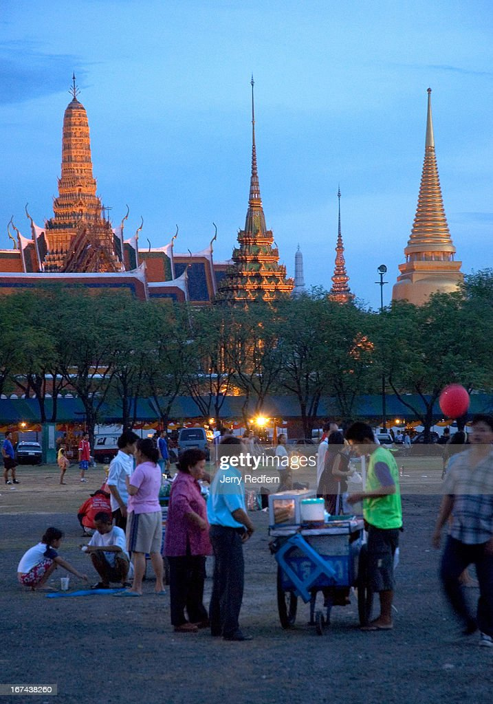 A snack vendor prepares a hot nosh for customers at Sanam Luang, with the Royal Palace in the background..
