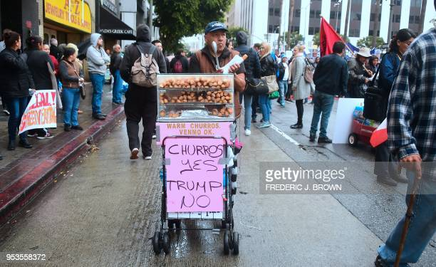 TOPSHOT A snack vendor sells churros demonstrators march through the city during May Day protests in Los Angeles California on May 1 2018