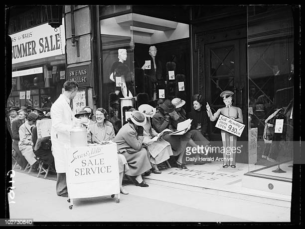 Snacks as the bargain hunters wait 1938 A photograph of a man serving snacks to shoppers waiting outside Swears Wells London for their summer sale to...