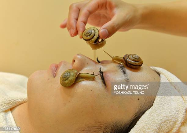 Snails crawls on the face of a woman for the demonstration of a new beauty treatment at the beauty salon 'CizLabo' in Tokyo on July 13 2013 as the...