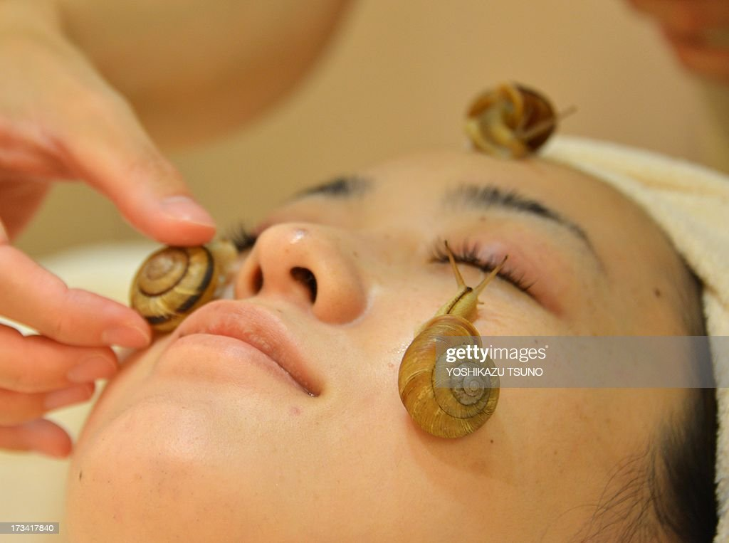 Snails crawls on the face of a woman for the demonstration of a new beauty treatment at the beauty salon 'Ci:z.Labo' in Tokyo on July 13, 2013 as the salon will start the new service from July 15. 'Slime from snails helps remove old cells, heal the skin after sun burn and moisturise it,' said Manami Takamura, a beauty salon employee, as she placed three gastropods on a woman's face. AFP PHOTO / Yoshikazu TSUNO